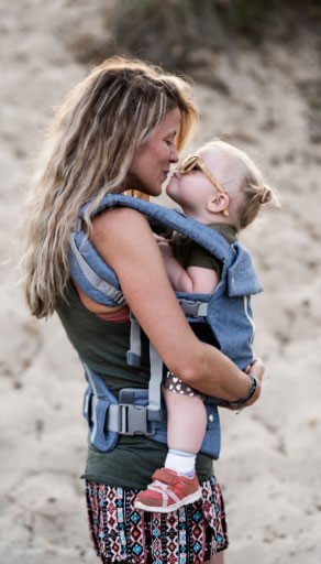 mum hugging cute toddler at the beach